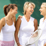 3 women on tennis tennis court holding their racquets