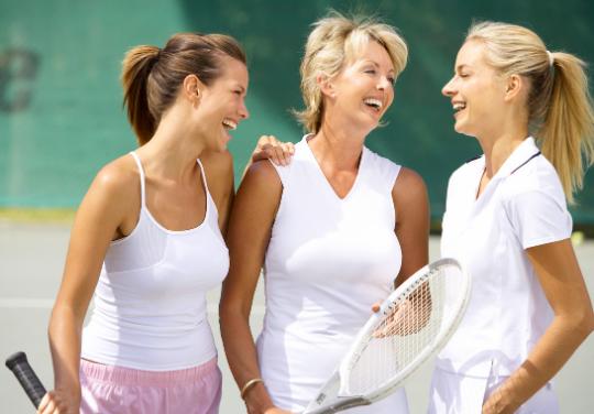 3 women on tennis tennis court holding their racquets